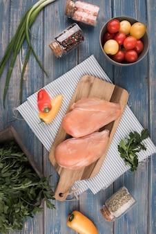 Pechuga de pollo plana sobre tabla de madera con pimientos y tomates