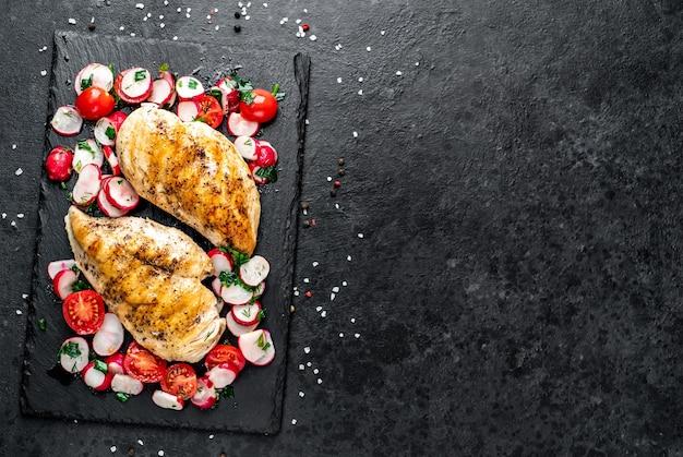 Pechuga de pollo a la plancha y ensalada con verduras frescas tomates y rábanos carne de pollo con ensalada comida sana en mesa de piedra