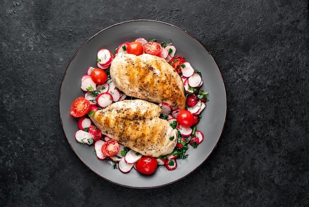 Pechuga de pollo a la plancha y ensalada con verduras frescas tomates y rábanos en un plato carne de pollo con ensalada comida sana en mesa de piedra