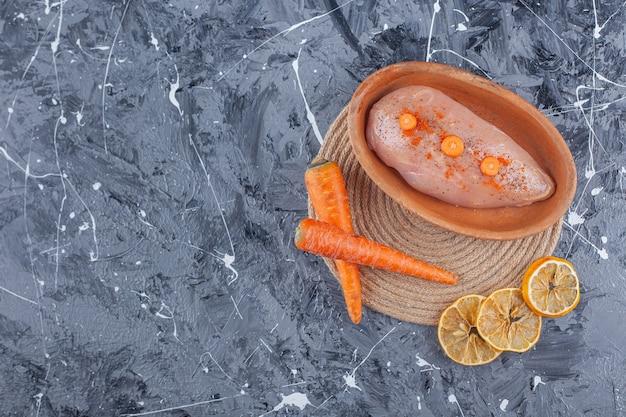 Pechuga de pollo en un recipiente junto a las zanahorias y el limón sobre un salvamanteles sobre la superficie azul
