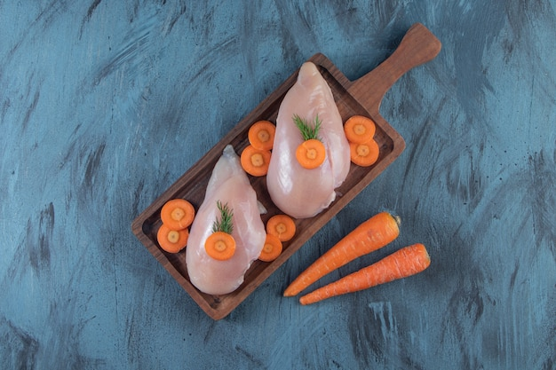 Pechuga de pollo y zanahorias en una tabla, sobre la superficie azul.