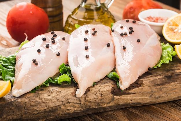 Pechugas de pollo crudas y especias sobre tabla para cortar madera