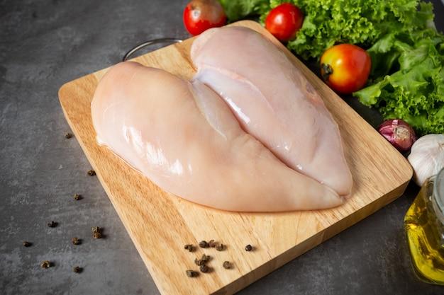 Pechugas de pollo crudas en tabla de cortar de madera.