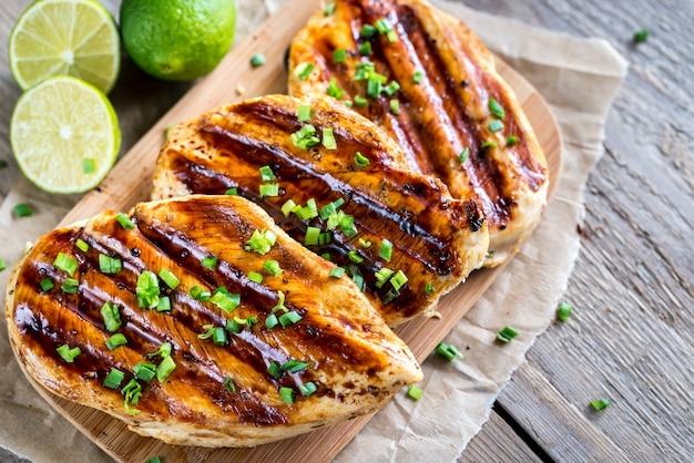Pechugas de pollo a la plancha en salsa de lima sobre fondo rústico