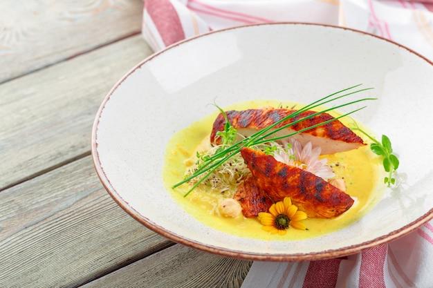 Pechugas de pollo sanas a la parrilla marinadas cocinadas en una barbacoa de verano y servidas con hierbas frescas