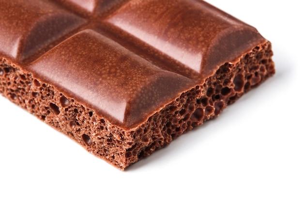 Pedazo de barra de chocolate aireada de cerca sobre fondo blanco.
