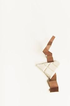 Pedazo blanco del chocolate en el papel marrón doblado de la tarjeta contra el fondo blanco