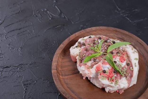 Pedazo de carne cruda en placa de madera decorada con menta fresca sobre fondo oscuro.