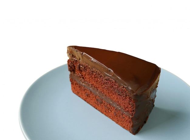 Pedazo de delicioso pastel de chocolate de capa corta servido en un plato azul aislado sobre fondo blanco