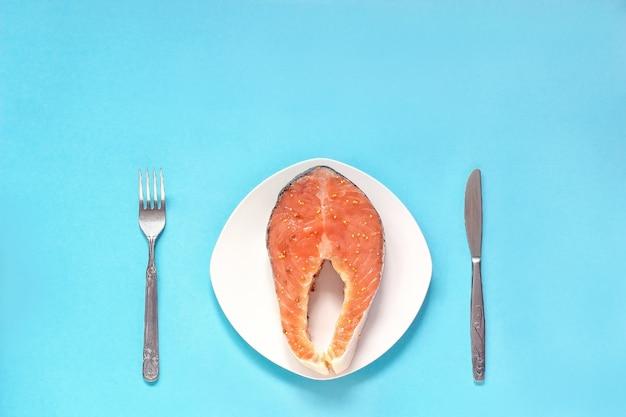 Pedazo de filete de pescado rojo marinado en plato blanco con cuchillo y tenedor.
