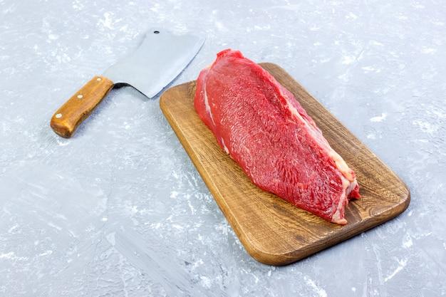 Pedazo grande fresco de carne de res en una tabla de cortar de madera