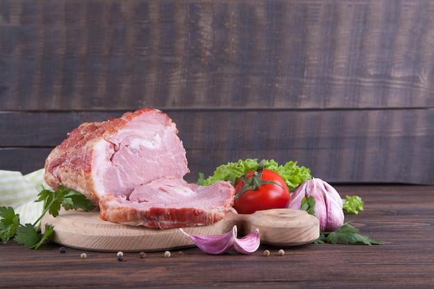 Un pedazo de jamón y de verduras en un fondo de madera. producto de la carne