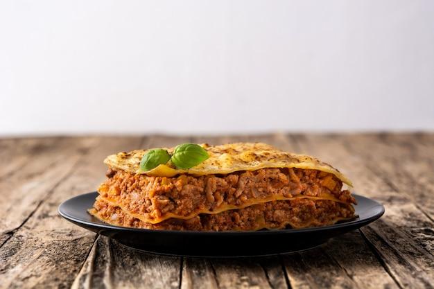Pedazo de lasaña de carne en mesa de madera