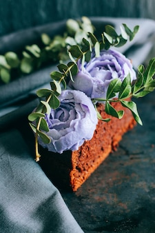 Pedazo de pastel de chocolate de cumpleaños con rosas crema púrpuras