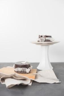 Un pedazo de pastel de chocolate con una envoltura en una tabla de cortar y un soporte para pasteles en el escritorio gris