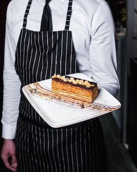 Pedazo de pastel con glaseado de chocolate y maní encima