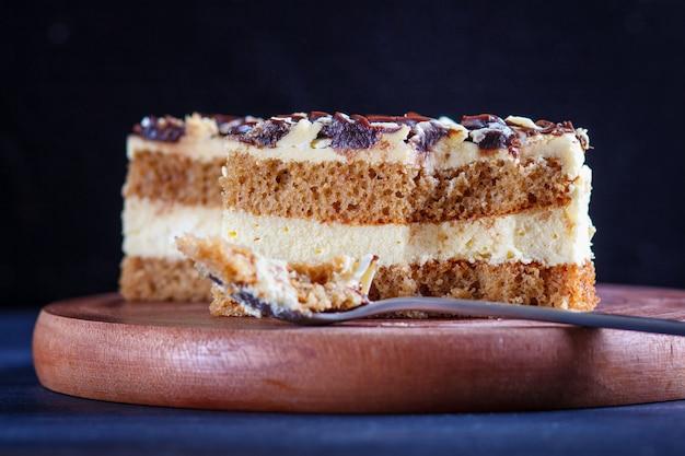 Un pedazo de pastel con leche y crema de mantequilla cortada con una cuchara en una tabla de cocina de madera, mesa negra.
