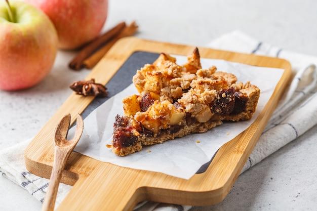 Pedazo de pastel de manzana vegana con canela y dátiles. concepto de comida vegana