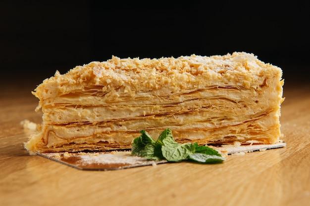 Pedazo de pastel de napoleón en la mesa de madera