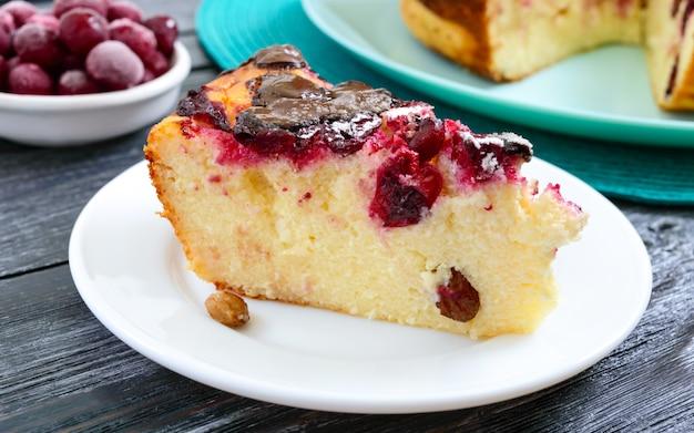 Pedazo de pastel de requesón con cerezas y gotas de chocolate en un plato sobre una superficie de madera.