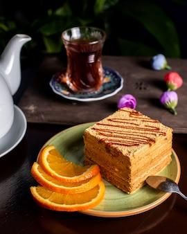 Pedazo de pastel servido con rodajas de naranja servidas con té 1
