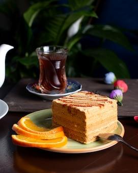Pedazo de pastel servido con rodajas de naranja servidas con té