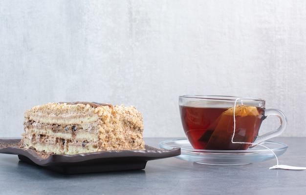 Un pedazo de pastel con una taza de café aromático en la mesa gris.