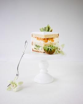 Pedazo de pastel de vainilla con kiwi fresco y duraznos en cakestand de madera blanca
