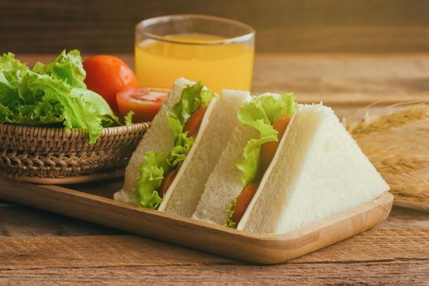 Pedazo de queso sándwich de jamón con lechuga y tomate en plato de madera