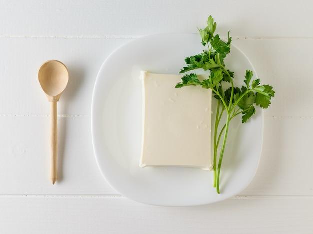 Pedazo rebanado de queso servio con perejil en una placa.