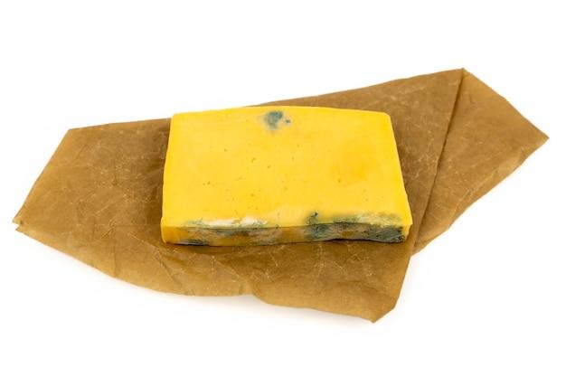 Pedazo rectangular de queso mohoso sobre papel artesanal aislado sobre fondo blanco.