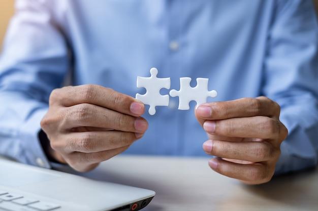Pedazo del rompecabezas de los pares de conexión de la mano del hombre de negocios en oficina.