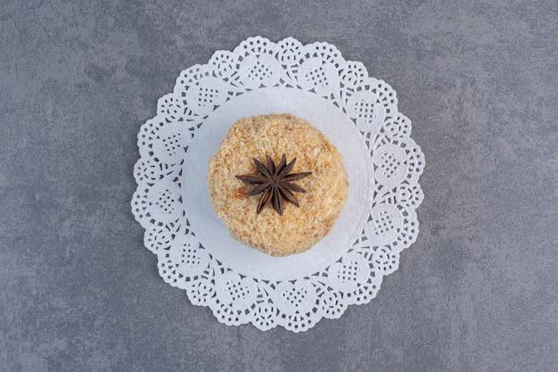 Pedazo de tarta casera decorada con clavo sobre superficie de mármol.
