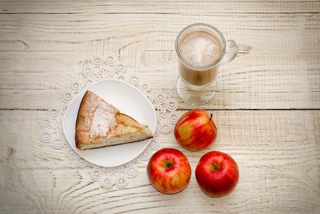 Pedazo de tarta de manzana, capuchino y manzanas maduras en una mesa de madera clara, vista superior