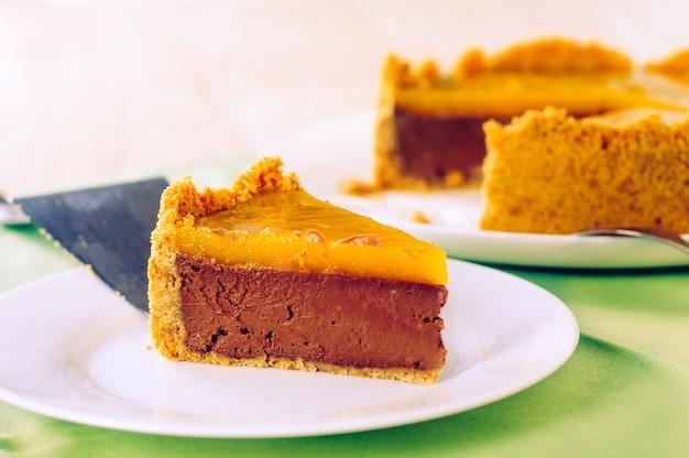 Pedazo de tarta de queso con caramelo de chocolate casero sobre mantel verde