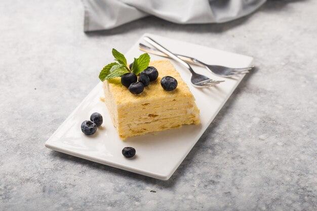 Pedazo de torta napoleon en la placa blanca en el fondo concreto, visión ascendente cercana. postre tradicional de milhojas con hojaldre y crema pastelera, copie el espacio.