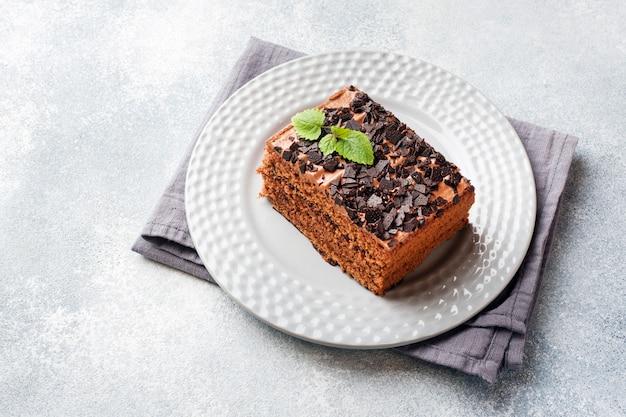 Un pedazo de torta de la trufa con el chocolate en un fondo concreto gris. copia espacio