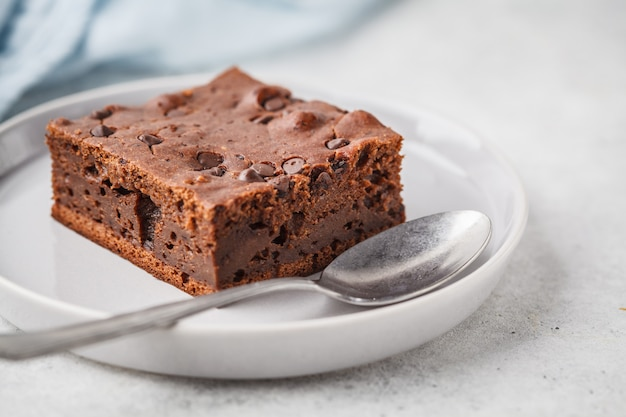 Pedazo de torta del vegano del chocolate con gotas y tuercas de chocolate.