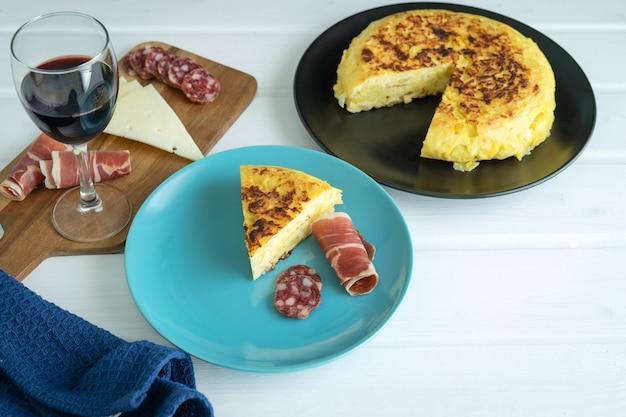 Pedazo de tortilla de patatas con jamón y salchicha en una placa azul con una tabla de quesos