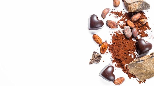 Pedazos de chocolate, granos de cacao, bastón de caramelos en un fondo aislado blanco.