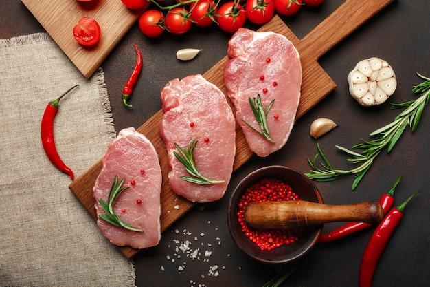 Pedazos de filete de cerdo crudo en la tabla de cortar con tomates cherry, romero, ajo, pimienta, sal y especias mortero sobre fondo marrón oxidado