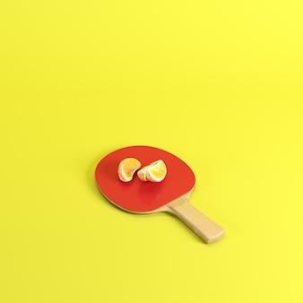 Pedazos de fruta pelada fresca de la mandarina o mandarina en la paleta del ping-pong aislada en fondo amarillo