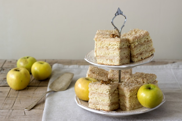 Pedazos de tarta de manzana y manzanas en una mesa de madera. estilo rústico