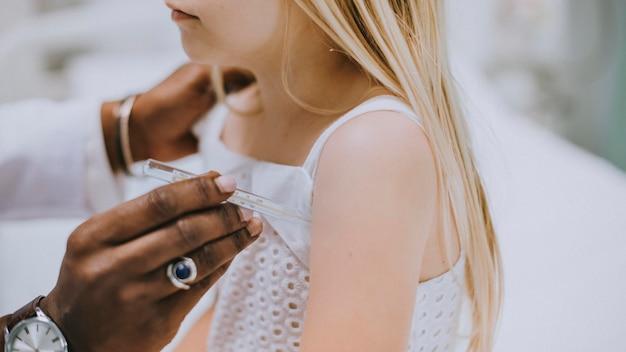 Pediatra comprobando los latidos del corazón de una niña