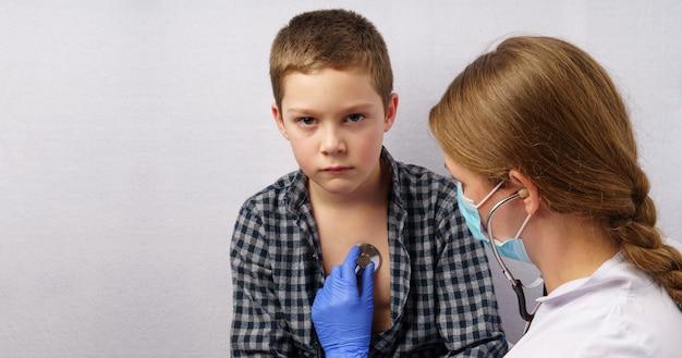 El pediatra escucha el tórax del niño con un estetoscopio.