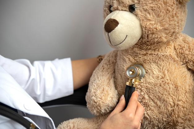 Pediatra irreconocible examinar osito de peluche con ayuda de estetoscopio