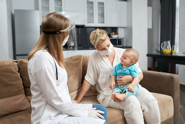 Pediatra en máscara médica visitando al bebé en casa