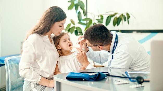 Pediatra masculino examina a la niña durante la visita médica con su madre