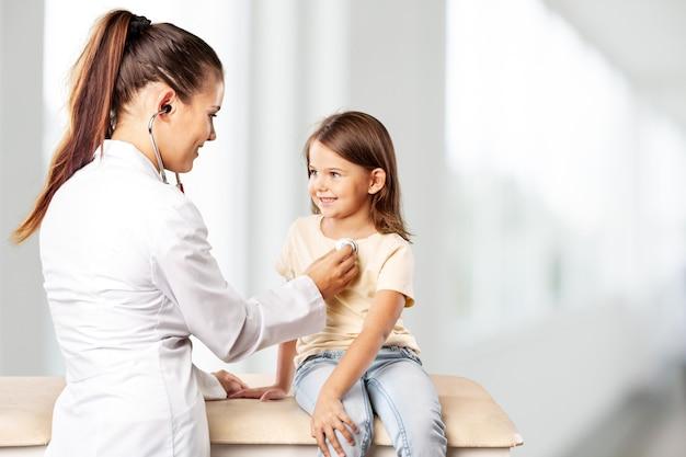 Pediatra masculino mantenga estetoscopio examen niño niño paciente visita al médico con la madre,
