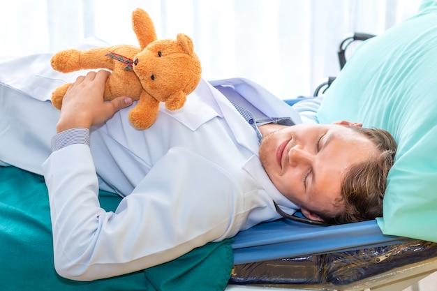 Pediatra (médico) durmiendo y abrazo cerveza de peluche en el hospital de la habitación. buen sueño y relájate.